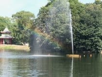 a fountain causing a rainbow on a pond