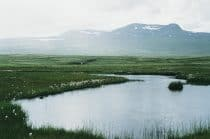 a view of a mountain with water across grasslands